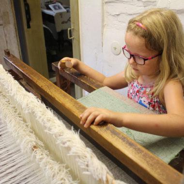 Mädchen webt an einem Webstuhl