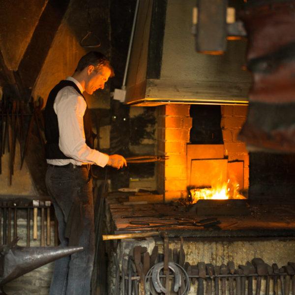 Schmied bei der Arbeit am offenen Feuer