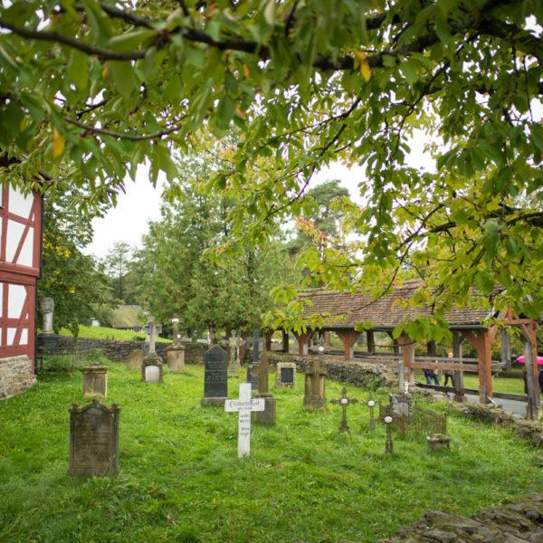 Blick auf den Kirchhof der Kirche aus Niederhörlen mit gesammelten Grabsteinen. Im VOdergrund ein weißes Kreuz.