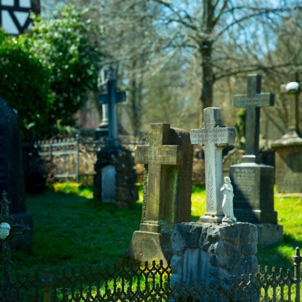 Blick auf den Kirchhof bei der Kirche aus Niederhörlen mit gesammelten Grabsteinen