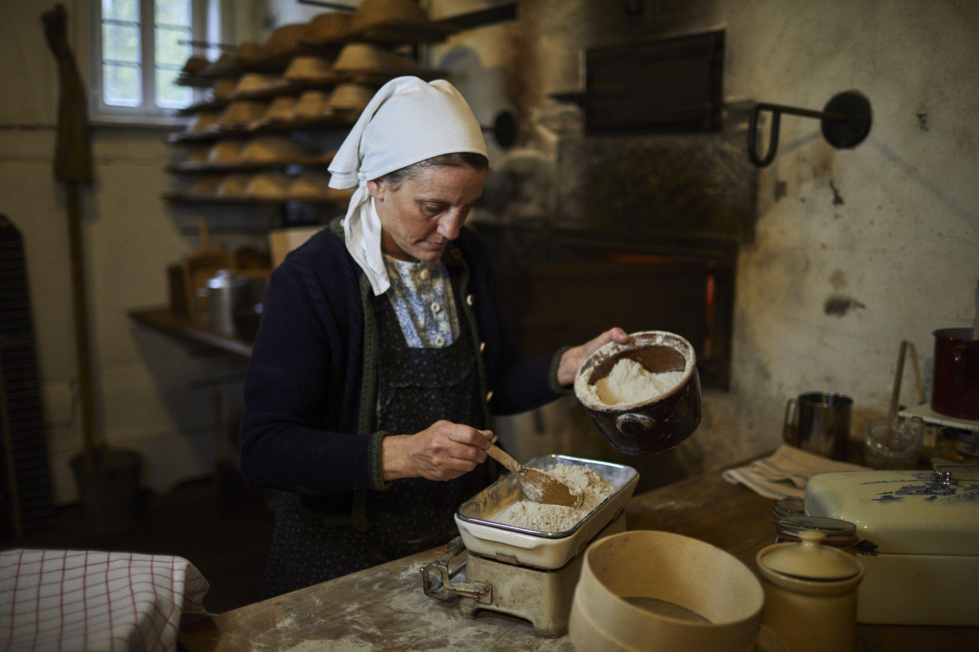 Bäckerin backt Brot im Backhaus