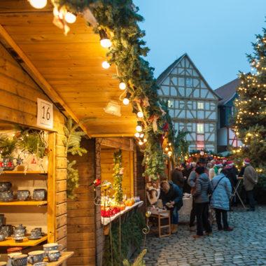 Beleuchtete Holzhütten auf dem Adventsmarkt