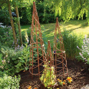 In einem Garten stehen zwei Rankhilfen in verschiedenen Größen. Diese kann man bei einem Kurs im Hessenpark selbst herstellen.