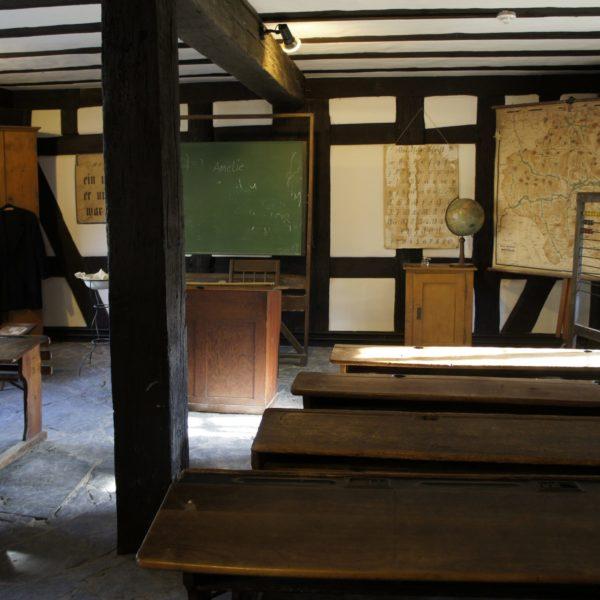 Das Schulhaus von innen mit Blick zur Tafel. Dahinter Landkarten.