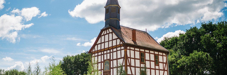 Kirche aus Ederbringhausen vor sonnigem, bewölktem Himmel