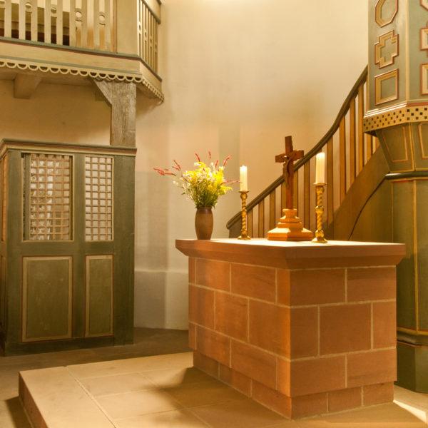 Mit Blumenstrauß und Kerzen geschmückter Altar aus Stein