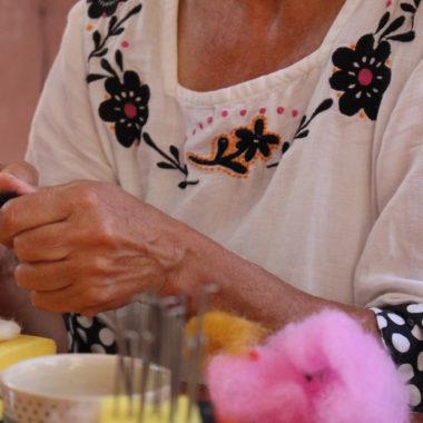 Eine Handwerkerin formt mit ihren Händen ein Stück Filz.