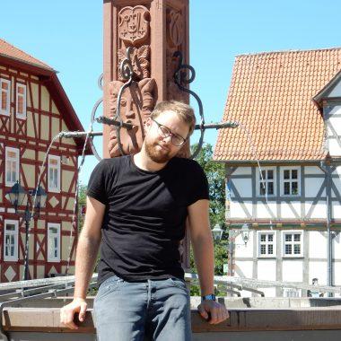 Poetry Slammer Lars Ruppel am Brunnen auf dem Marktplatz des Hessenparks.