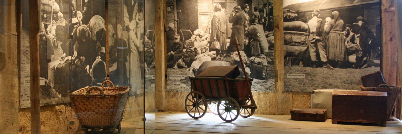 """In der Scheune aus Damshausen ist die Dauerausstellung zum Thema """"Flucht und Vertreibung"""" zu sehen. An den Wänden hängen ausdrucksstarke Bilder. Außerdem sind mehrere Objekte im Raum platziert."""