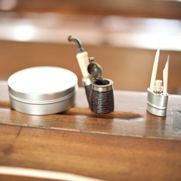 Detailaufnahme vom Lehrerpult mit Pfeife, Tabakdose und Schreibfeder