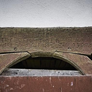 Holzbalken eines Fachwerkbaus mit geschnitzter Schrift