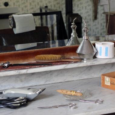 Spiegelanrichte mit Friseurutensilien im historischer Friseursalon