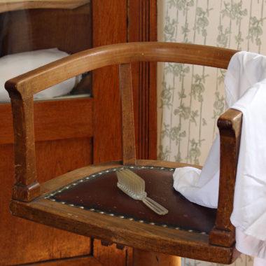 Haarbürste und Kittel auf einem historischen Frisierstuhl