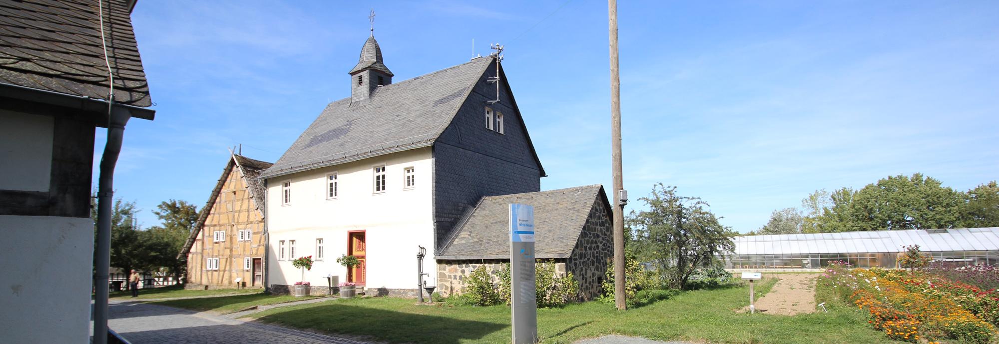 Verputztes Haus mit Wetterfront und kleinem Nebengebäude. Das Hauptgebäude hat eine rot-gelbe Haustür, davor stehen links und rechts zwei Rosenstöcke.