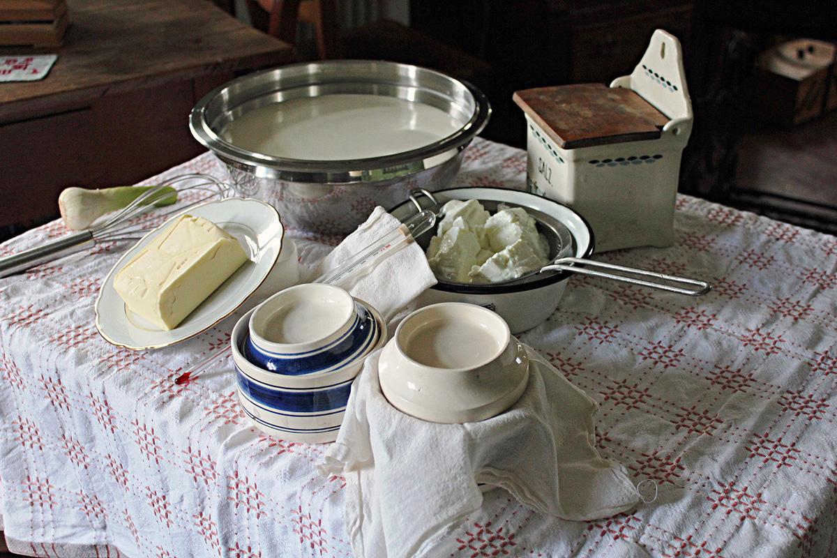 Milch, Butter, Käse und Küchenutensilien auf einem Tisch