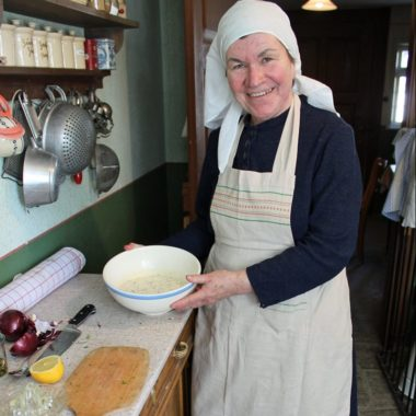 Historische Hausfrau mit Soßenschüssel in der Küche