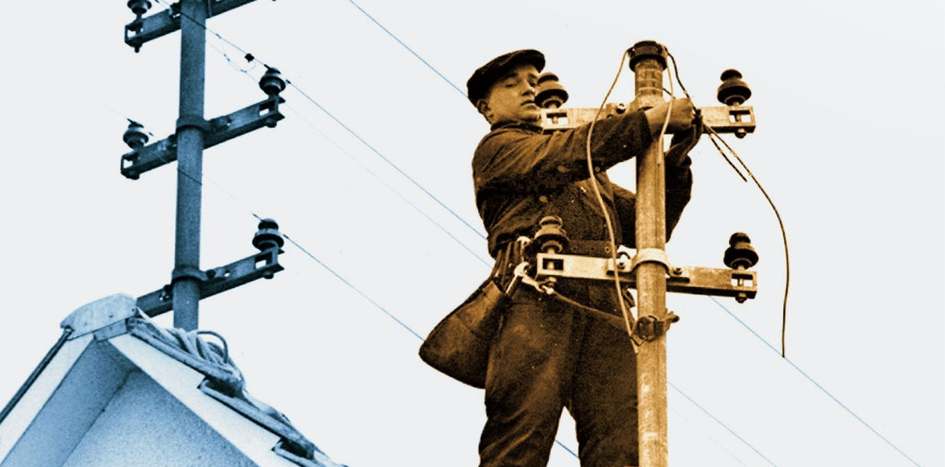 Zwei Männer arbeiten an den Stromantennen auf einem Häuserdach.