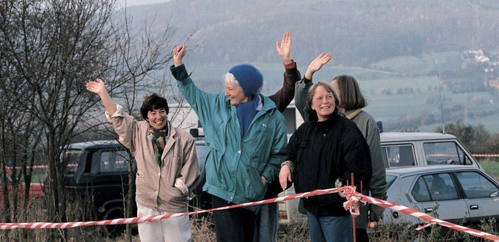 Anwohnerinnen winken auf westlicher Seite einfahrenden Autos aus der DDR zu