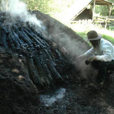Köhler beim Abtragen der Holzkohle aus dem Meiler