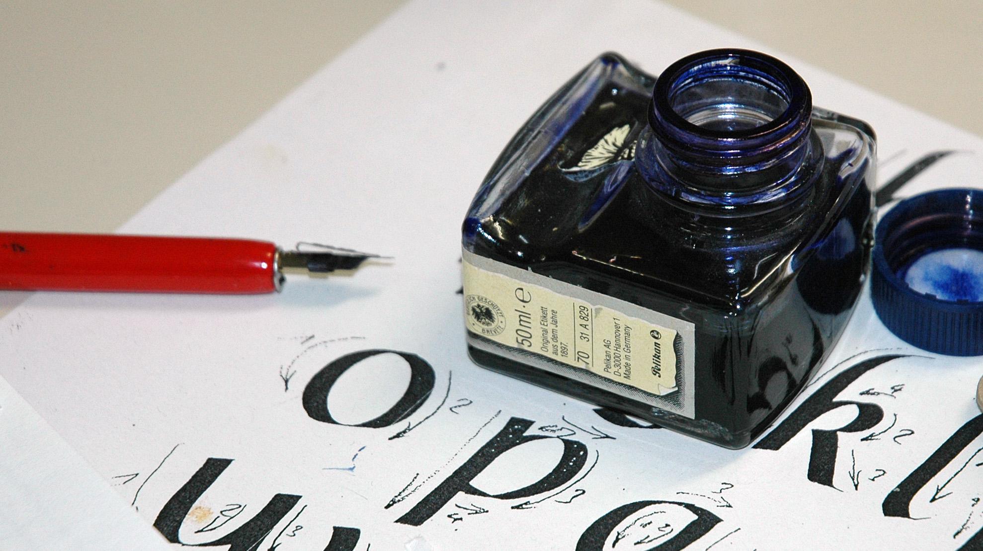 Federkiel, Tintenfass und Übungsblatt mit kalligrafischer Schrift
