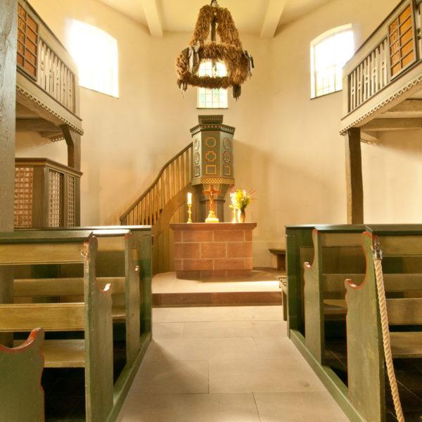 Gang zwischen den Sitzbänken in der Kirche aus Ederbringhausen mit Blick auf den Altar