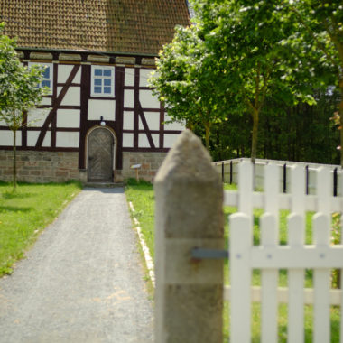 Weg mit kleiner Baumallee vor der Kirche aus Kohlgrund