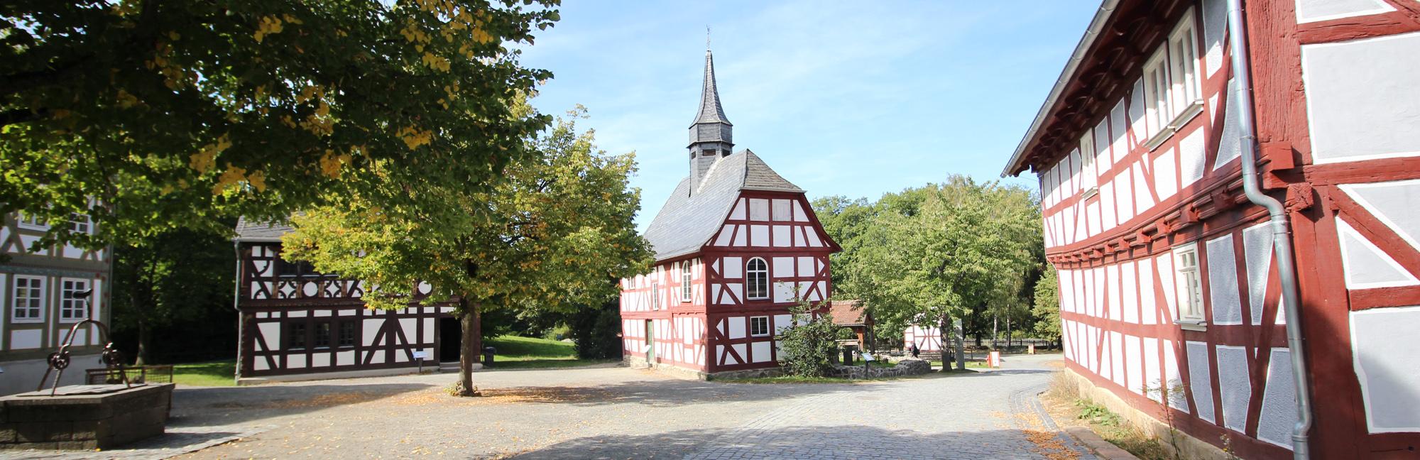 Fachwerkkirche am Dorfplatz mit Brunnen