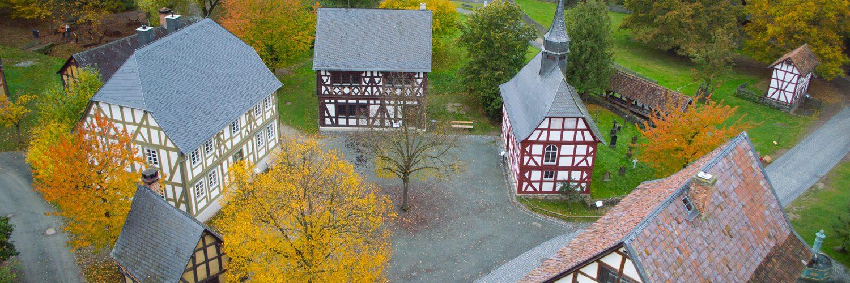 Blick auf den Dorplatz von oben. Rechts von der Mitte ist die Kirche aus Niederhörlen zu sehen.