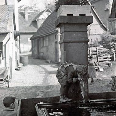 Kind trinkt Wasse am Brunnen.