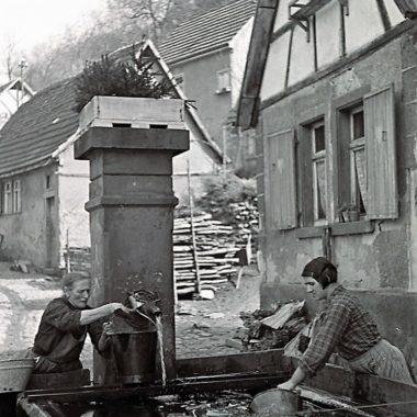 Hausarbeit am Brunnen.