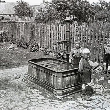 Brunnen in einer Gartenanlage mit drei Jungen.