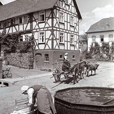 Eine Frau spült ihre Wäsche am Brunnen.