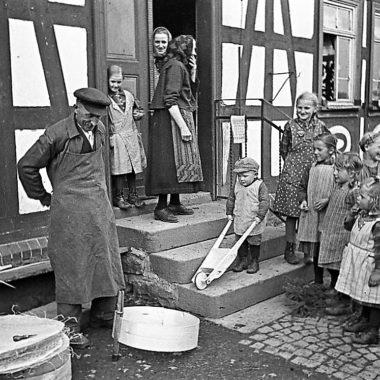 Kinder schauen einem Siebmacher bei der Arbeit zu.