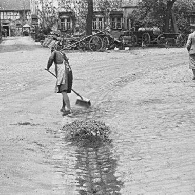 Mädchen beim Straßekehren.