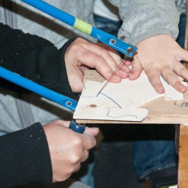 Kinderhände mit Laubsäge und Holzplatte