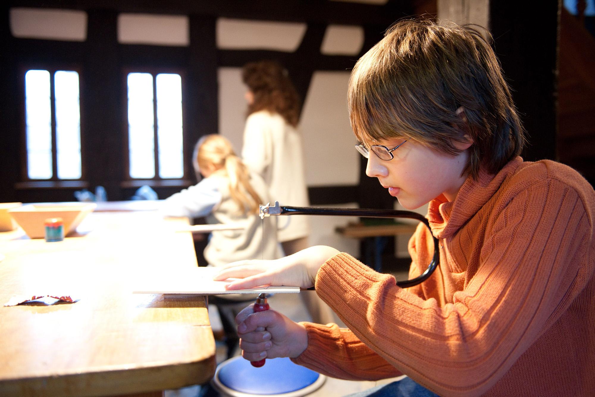 Ein Junge sägt ein Motiv an einem Tisch aus.