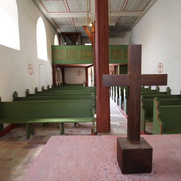 Innenaufnahme der Kapelle aus Lollar: Altar mit Holzkreuz, Blick auf grüne Kirchenbänke.