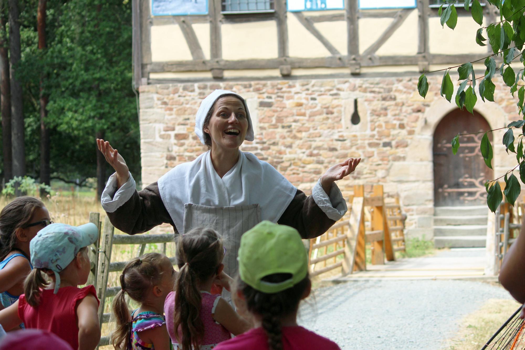 Die Märchenerzählerin steht vor einer Kindergruppe und erzählt aus einer Geschichte. Im Hintergrund sieht man eine Brücke und das Gebäude zu dem sie führt.