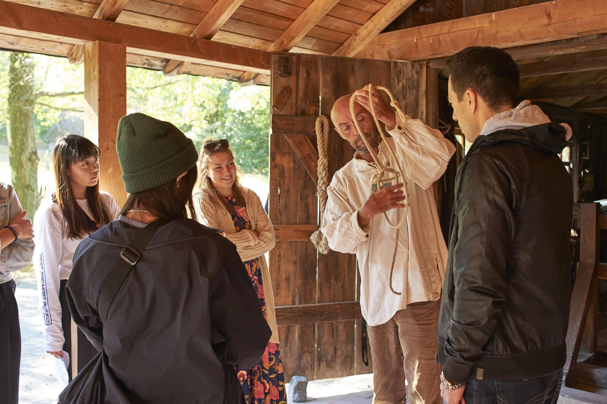 Der Vorführhandwerker in der Seilerei aus Gießen zeigt die Verwendung des gerade hergestellten Seiles. Um ihn herum versammeln sich etwa fünf interessierte Zuschauer.