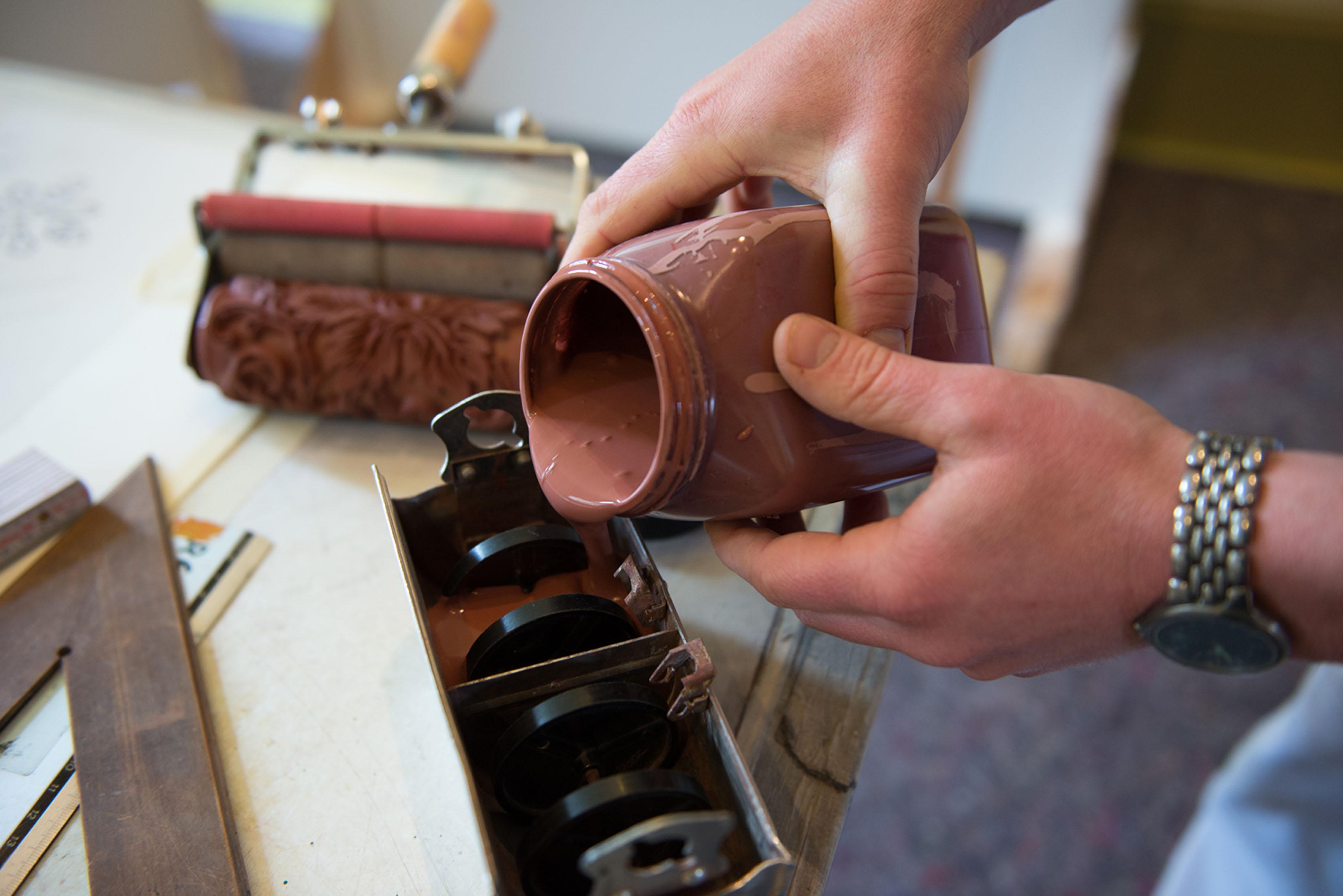 Maler beim Einfüllen von Farbe in das Rollgerät der Musterwalze