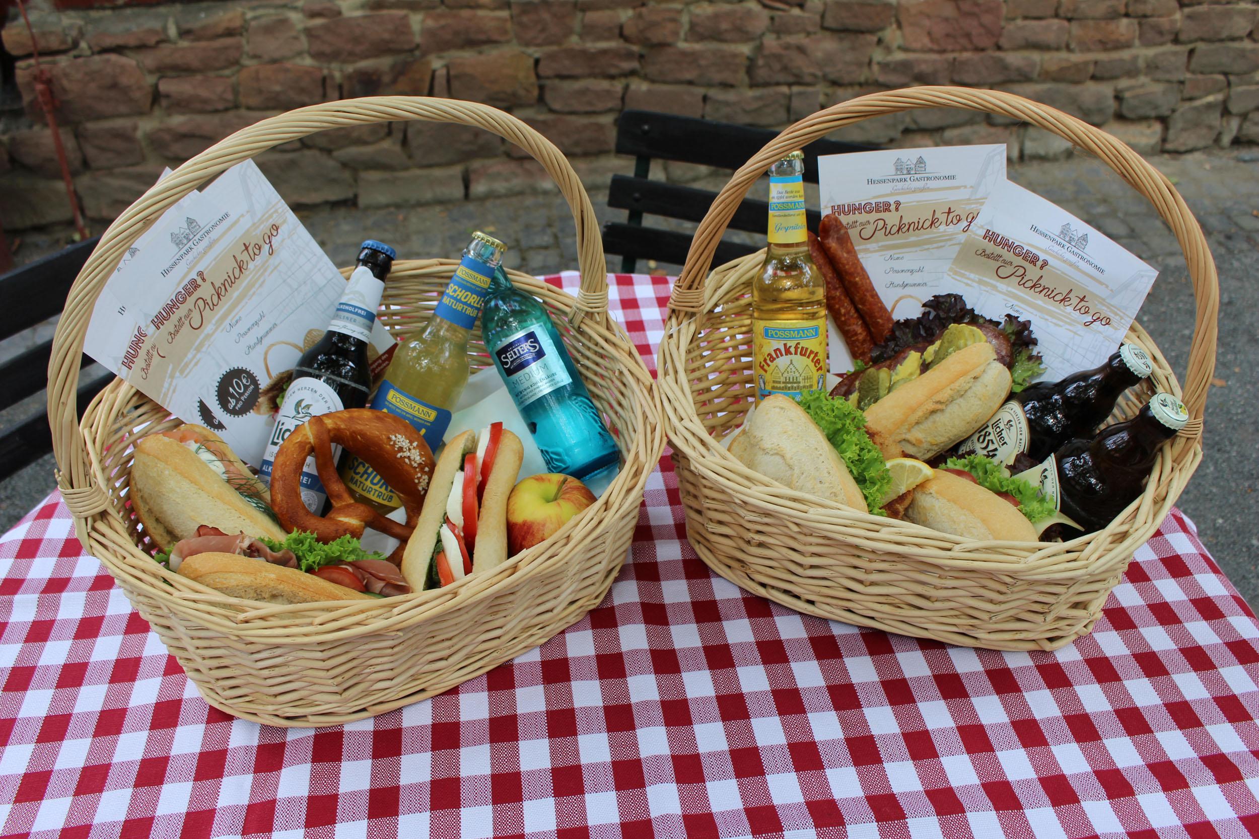 Zwei Picknick-Körbe mit diversen belegeten Brötchen und Getränken auf einem Tisch mit rot-weiß karrierter Tischdecke.
