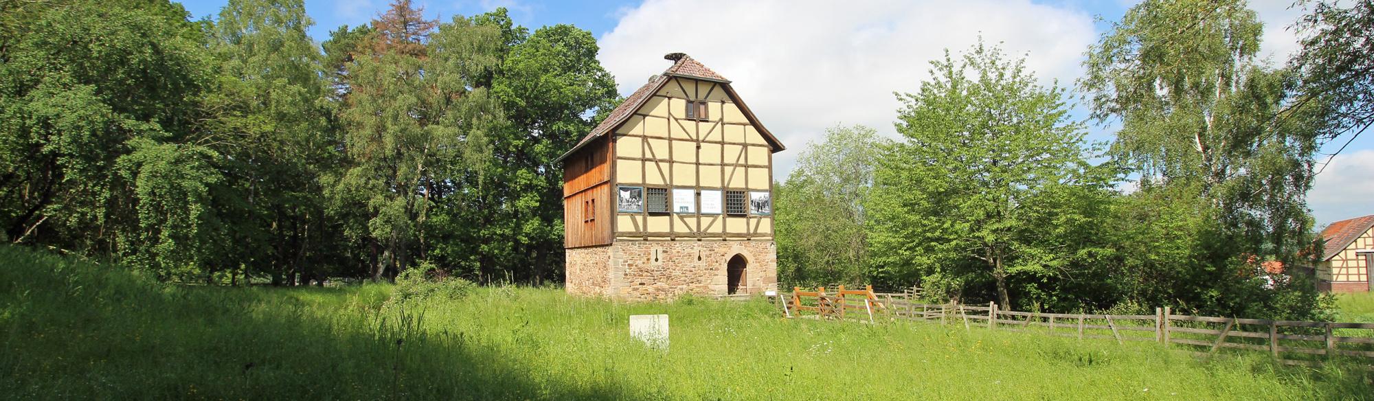 Ausstellungsgebäude Haus aus Ransbach von einem Wassergraben und Wiese umgeben.