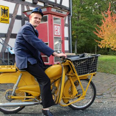 Rudi-Darsteller auf einem gelben Postmoped