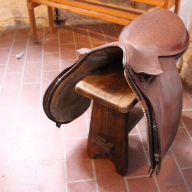 Über einem Holzhocker liegt ein Sattel in der Sattlerei
