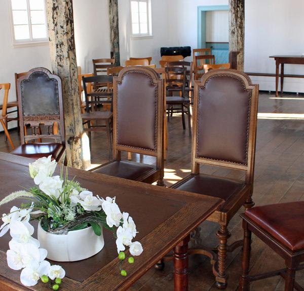 Innenaufnahme des Trauzimmers: Trautisch mit Blumendeko und gepolsterte Stühle