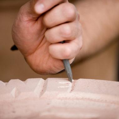 Hand mit Meißel beim Bearbeiten einen Steinblocks