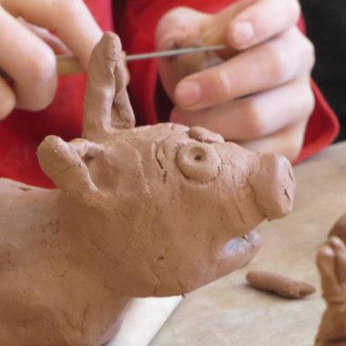 Kinderhände töpfern eine Tierfigur