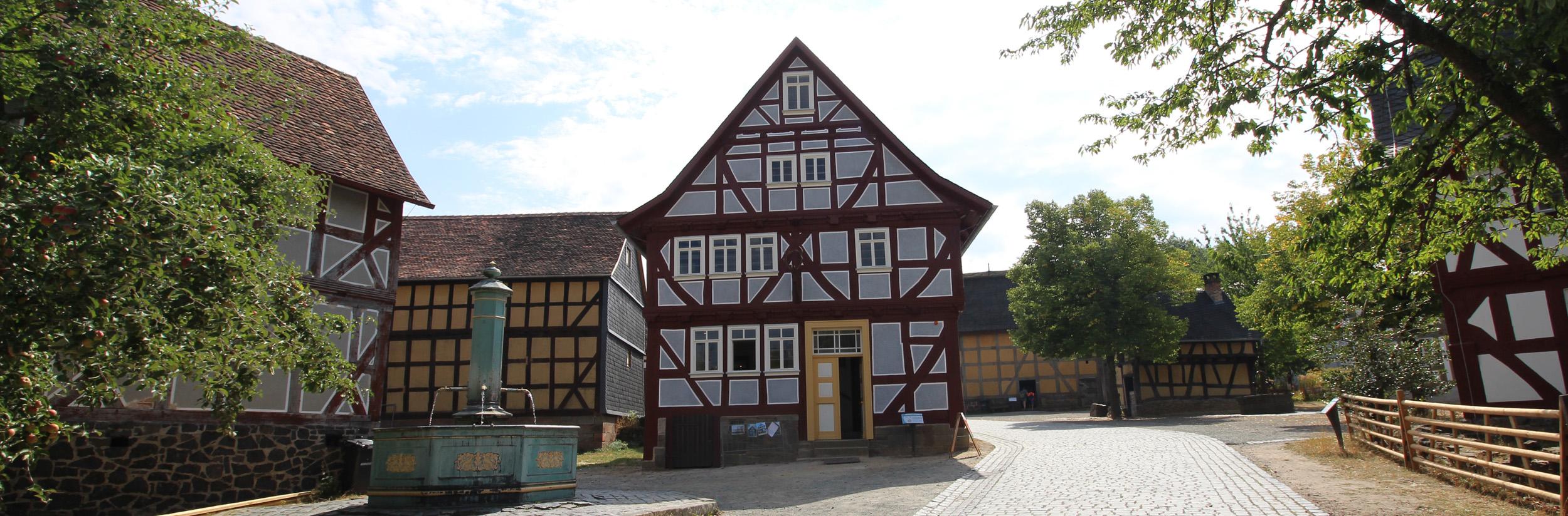 Vor der Stirnseite des Hauses aus Grebenau steht ein großer Brunnen. Links davon ein großer Apfelbaum.