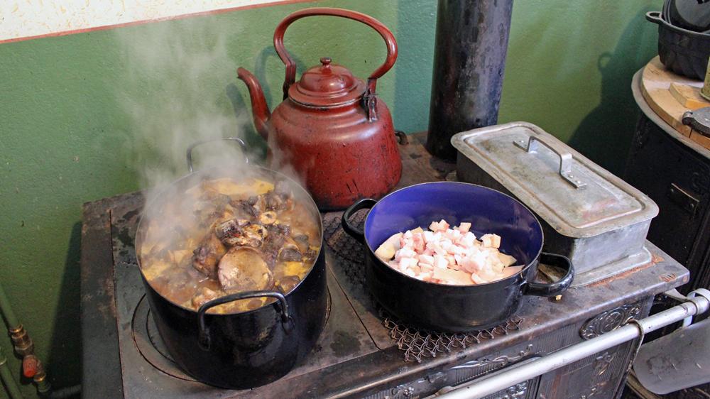 Fleischbrühe und Speck brutzeln auf dem Herd in Uromas Küche.