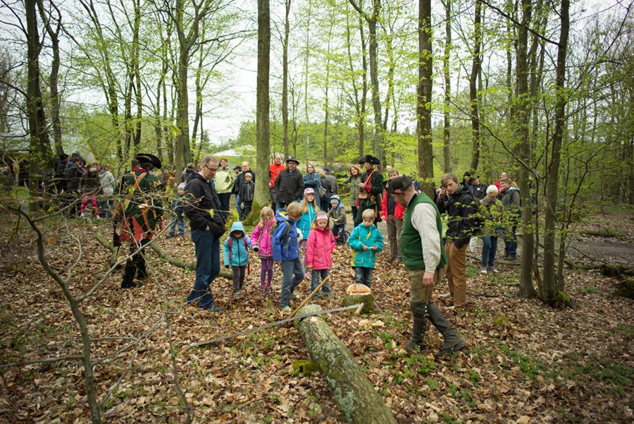 Besucher schauen historischen Forstjägern bei der Baufällung zu.